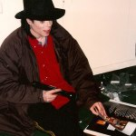 Michael in studio reading a book with flashlight during a brown-out